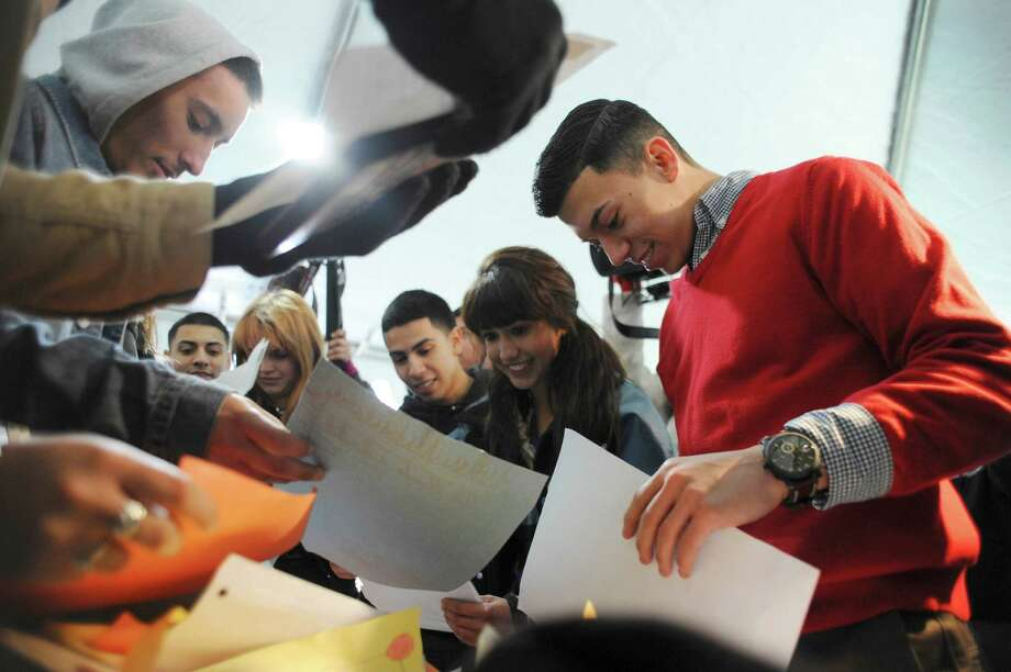 High school seniors on Tuesday, Feb. 24, 2015, examine the contents of a time capsule that they filled and buried in 2006, when they were third grade students at Palo Alto Elementary School. The students were told back then that they would receive full scholarships to Palo Alto College if they graduated from high school. Dr. Mike Flores, president of Palo Alto College, said that the 40 scholarships total over $225,000. The event marks the start of the 30th anniversary celebration of the creation of Palo Alto College. Photo: Billy Calzada, San Antonio Express-News / San Antonio Express-News