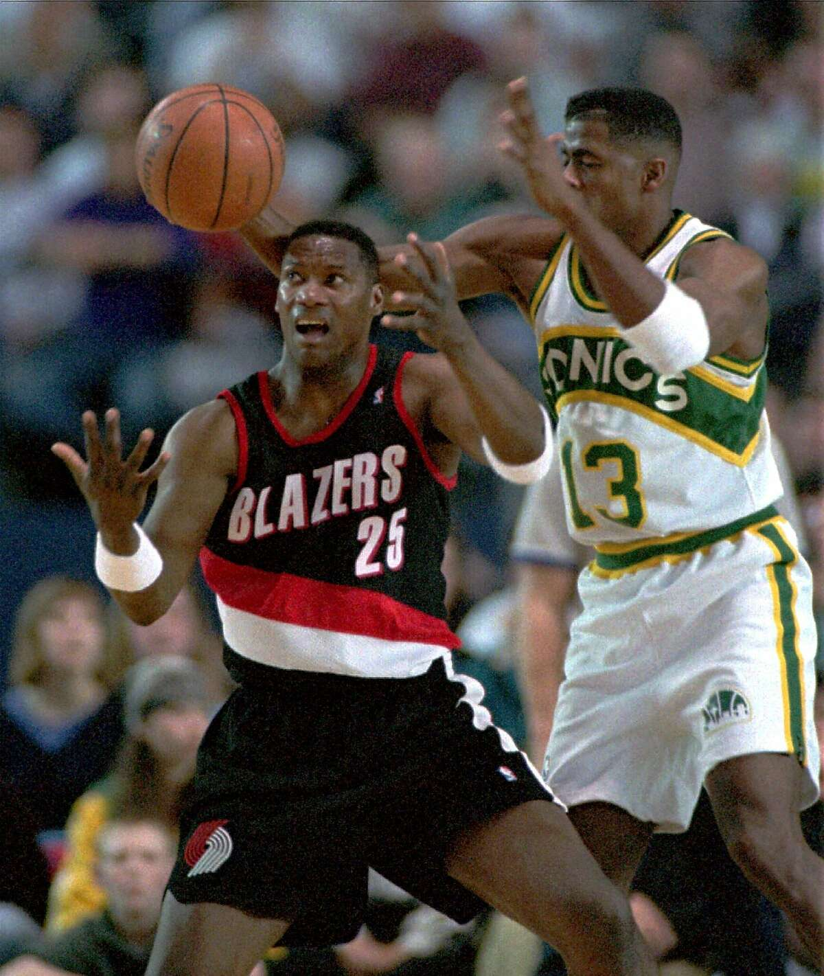 Kendall Gill (13) of the Seattle SuperSonics knocks the ball from the hands of Jerome Kersey (25) of the Portland Trail Blazers during the fourth quarter NBA action Monday, April 17, 1995, in Tacoma, Wash. Portland beat Seattle 97-93. (AP Photo/Gary Stewart)
