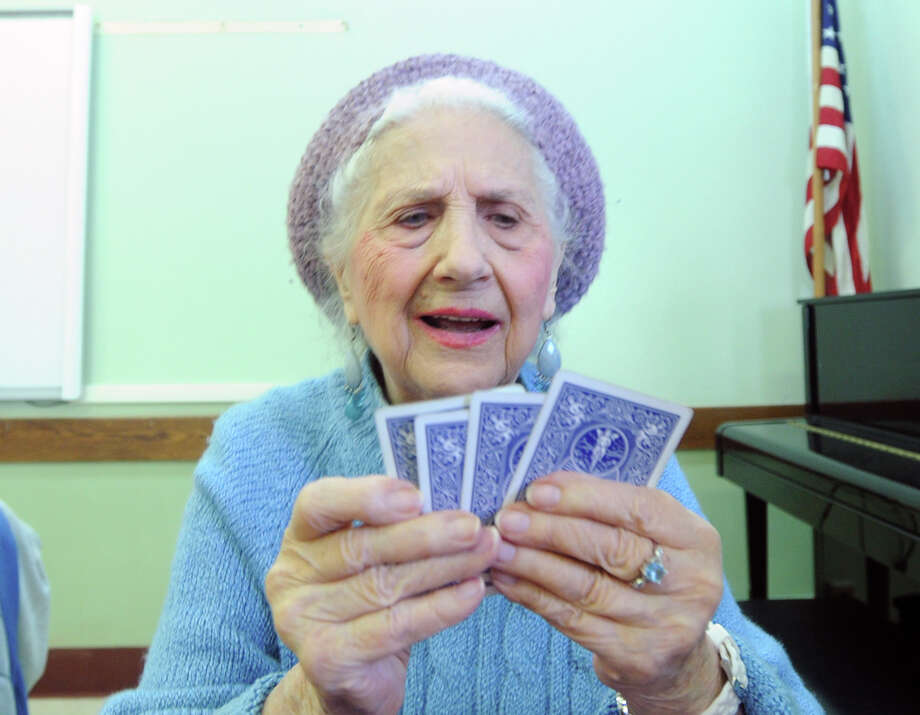 """Beating the artic cold, 97-year-old Alice Bey of Old Greenwich, plays a game of pairs with friends inside the Greenwich Senior Center in Greenwich, Conn., Tuesday afternoon, Feb. 24, 2015. """"I wanted to play poker but Eddie doesn't know how to play,"""" said Bey referring to one of the players at the table. Photo: Bob Luckey / Greenwich Time"""
