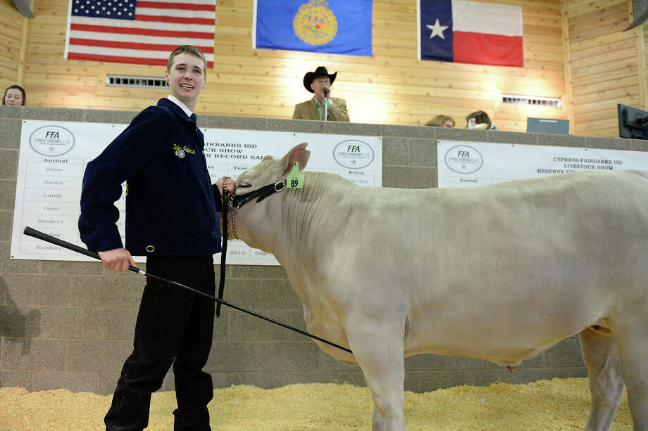 Cypress Woods High School sophomore Dylan Jebousek displays the grand champion market steer, which sold to Crane Rental Division Inc. for $55,000. Photo: Cfisd