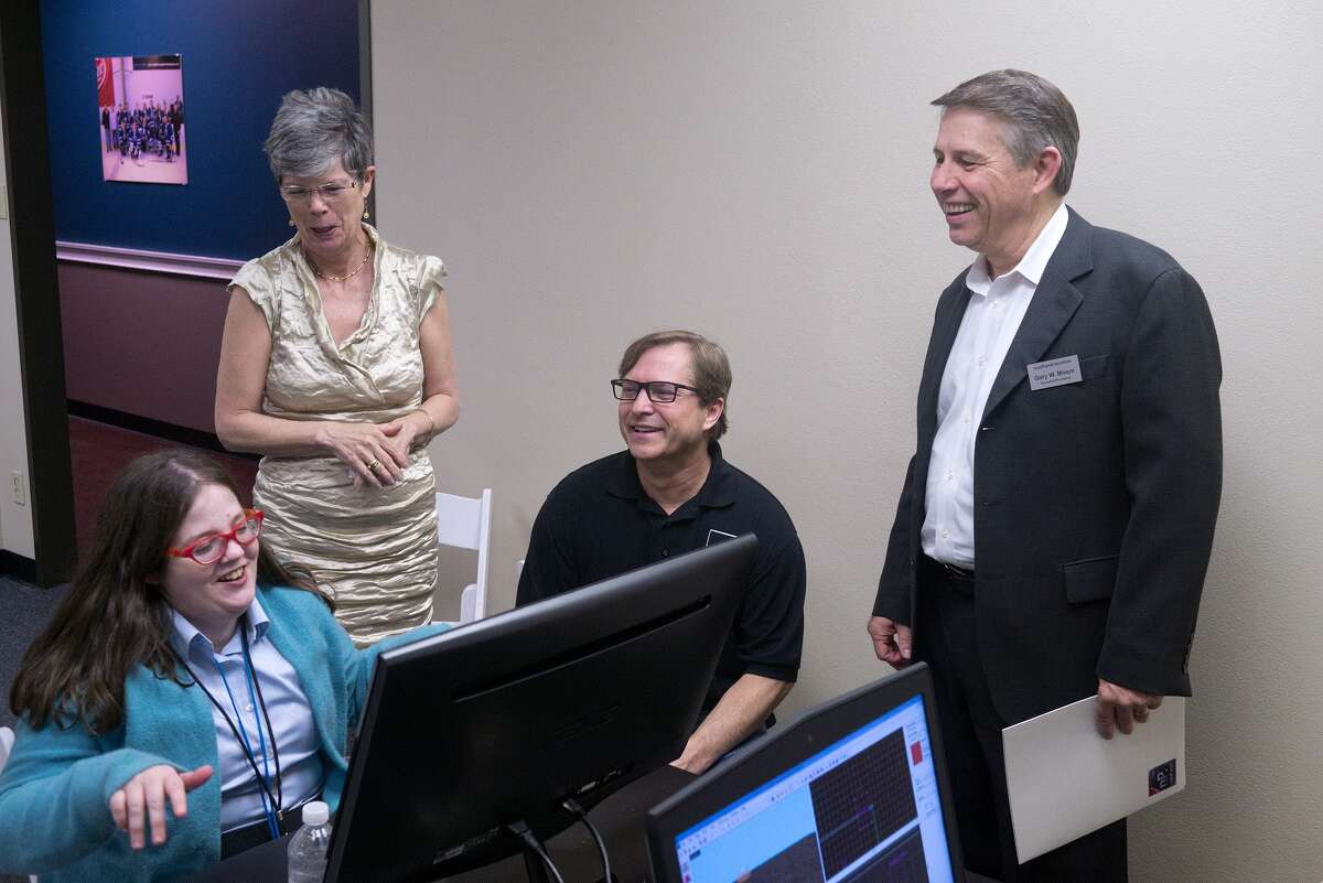 Katie Fergeson, left, talks with mother Norris Fergeson, and nonPareil Institute co-founders Dan Selec and Gary Moore during an open house for the planned campus of the institute, which provides support and training for adults with autism. spectrum.