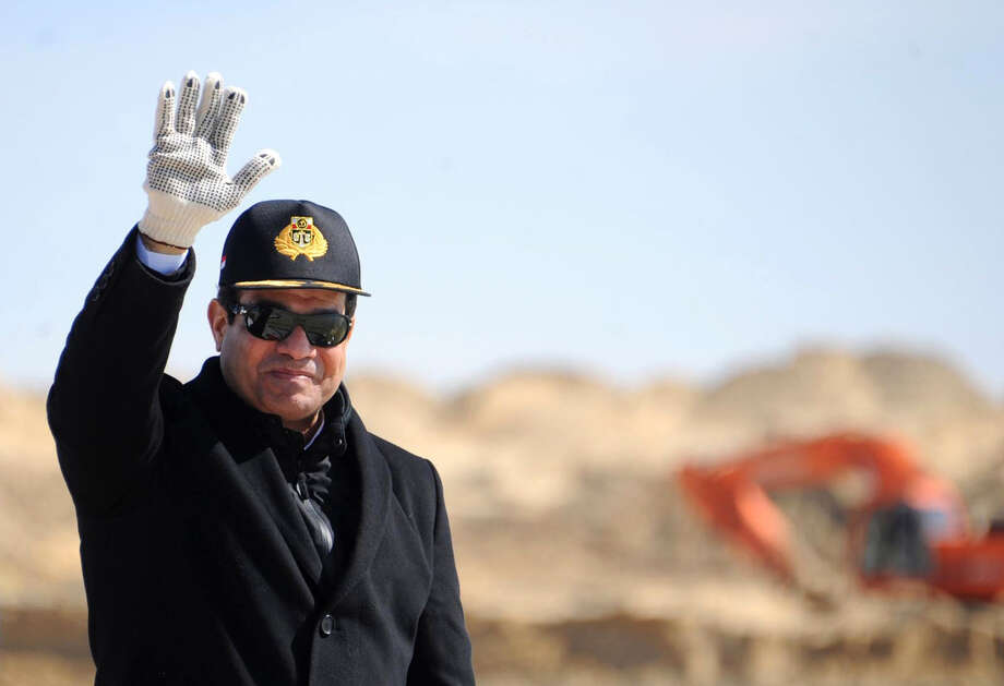 """Egyptian President Abdel-Fattah el-Sissi, right, waves during a visit to the Suez Canal in Ismailia, Egypt. El-Sissi issued a law that broadens the state's definition of terrorism to include anyone who threatens public order """"by any means,"""" and gives authorities powers to draw up lists of alleged terrorists with little judicial recourse. Photo: Uncredited / Associated Press / Egyptian Presidency"""