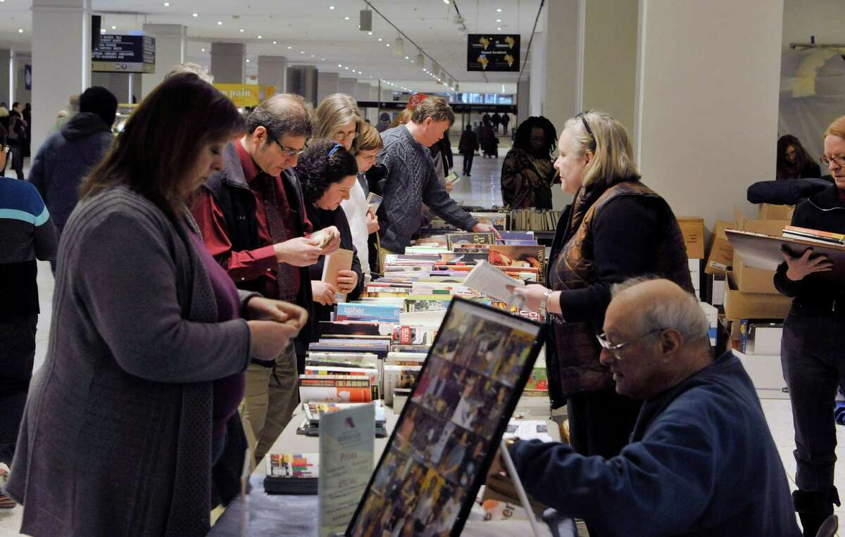 Shoppers look over the books for sale at the Help Fight Aids Through Books and Music sale on the concourse of the Empire State Plaza on Tuesday, Feb. 24, 2015, in Albany, N.Y. Steve Kozlowski started the fund raising event in 1993 as he was looking for a way to help people dealing with aids. The sale which is held three to four times a year at the plaza and two times a year outside The Book House in Albany, is run with donations of books and volunteers. Kozlowski said that to date the sales have raised about $750,000, which is given to the Alliance for Positive Health. The sale at the plaza runs through Friday. The next sale at the concourse starts on April 28th. (Paul Buckowski / Times Union)