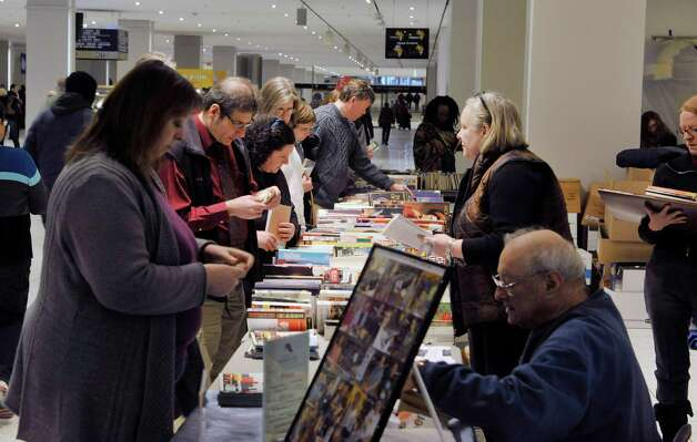 Shoppers look over the books for sale at the Help Fight Aids Through Books and Music sale on the concourse of the Empire State Plaza on Tuesday, Feb. 24, 2015, in Albany, N.Y.  Steve Kozlowski started the fund raising event in 1993 as he was looking for a way to help people dealing with aids.  The sale which is held three to four times a year at the plaza and two times a year outside The Book House in Albany, is run with donations of books and volunteers.  Kozlowski said that to date the sales have raised about $750,000, which is given to the Alliance for Positive Health.  The sale at the plaza runs through Friday.  The next sale at the concourse starts on April 28th.      (Paul Buckowski / Times Union) Photo: PAUL BUCKOWSKI / 00030679A