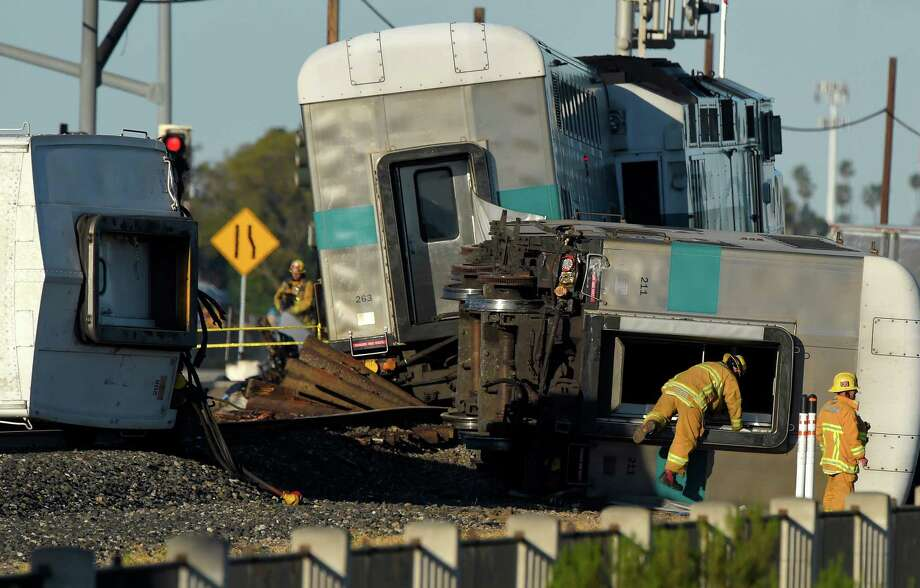 A firefighter climbs into the wreck of a Metrolink passenger train that derailed, Tuesday, Feb. 24, 2015, in Oxnard, Calif. Three cars of the Metrolink train tumbled onto their sides, injuring dozens of people in agricultural country 65 miles northwest of Los Angeles. Metrolink spokesman Scott Johnson told the Los Angeles Times that at least 30 people were injured. (AP Photo/Mark J. Terrill) Photo: Mark J. Terrill, STF / AP