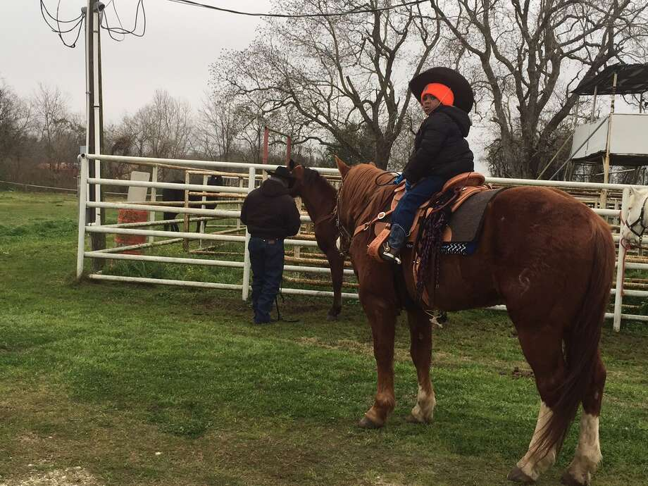 Jerry Henry Jr. on his horse with his dad, Jerry Henry Sr., behind him. Photo: Leah Binkovitz