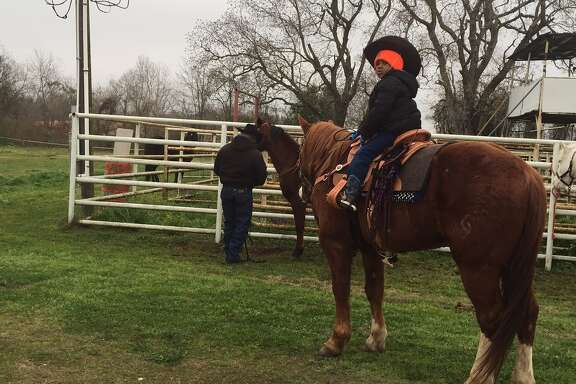 Jerry Henry Jr. on his horse with his dad, Jerry Henry Sr., behind him. They're part of the Northeastern Trail Riders.