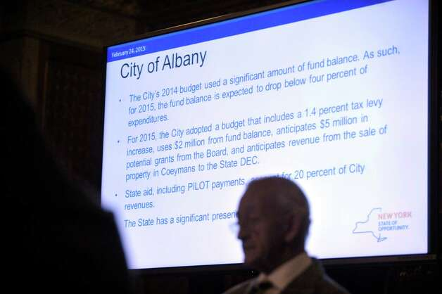 A slide on the screen shows information about the budget for the City of Albany as board members take part in a meeting of the Financial Restructuring Board of Local Governments at the Capitol on Tuesday, Feb. 24, 2015, in Albany, N.Y.  The board released their recommendations for several cities in the state.   (Paul Buckowski / Times Union) Photo: PAUL BUCKOWSKI / 00030725A