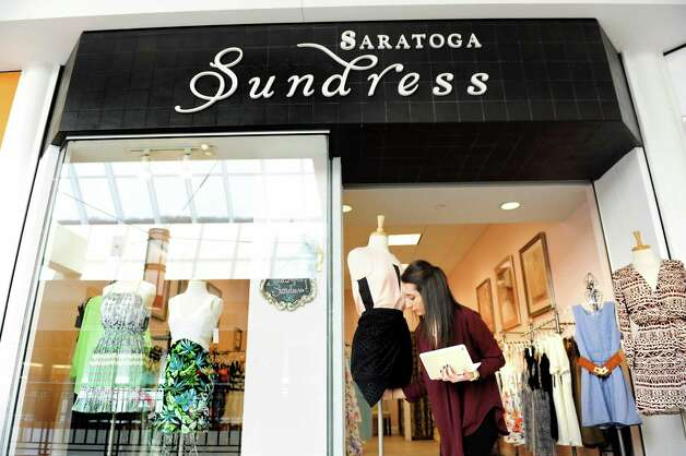 Assistant manager Monica Zecca woks on the display of the recently opened Saratoga Sundress on Tuesday, Feb. 24, 2015, at Colonie Center in Colonie, N.Y. The boutique-style store has been open for two months. (Cindy Schultz / Times Union) Photo: Cindy Schultz / 00030733A