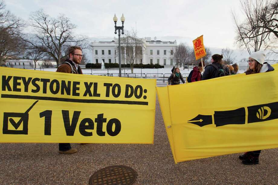 Danny Ruthenberg-Marshall (left), with 350 DC, and Lindsey Halvorson, 20, a student at American University, pick up their signs after attending a celebration Tuesday in support of President Barack Obama's veto of the Keystone legislation, outside the White House in Washington. Photo: Jacquelyn Martin /Associated Press / AP