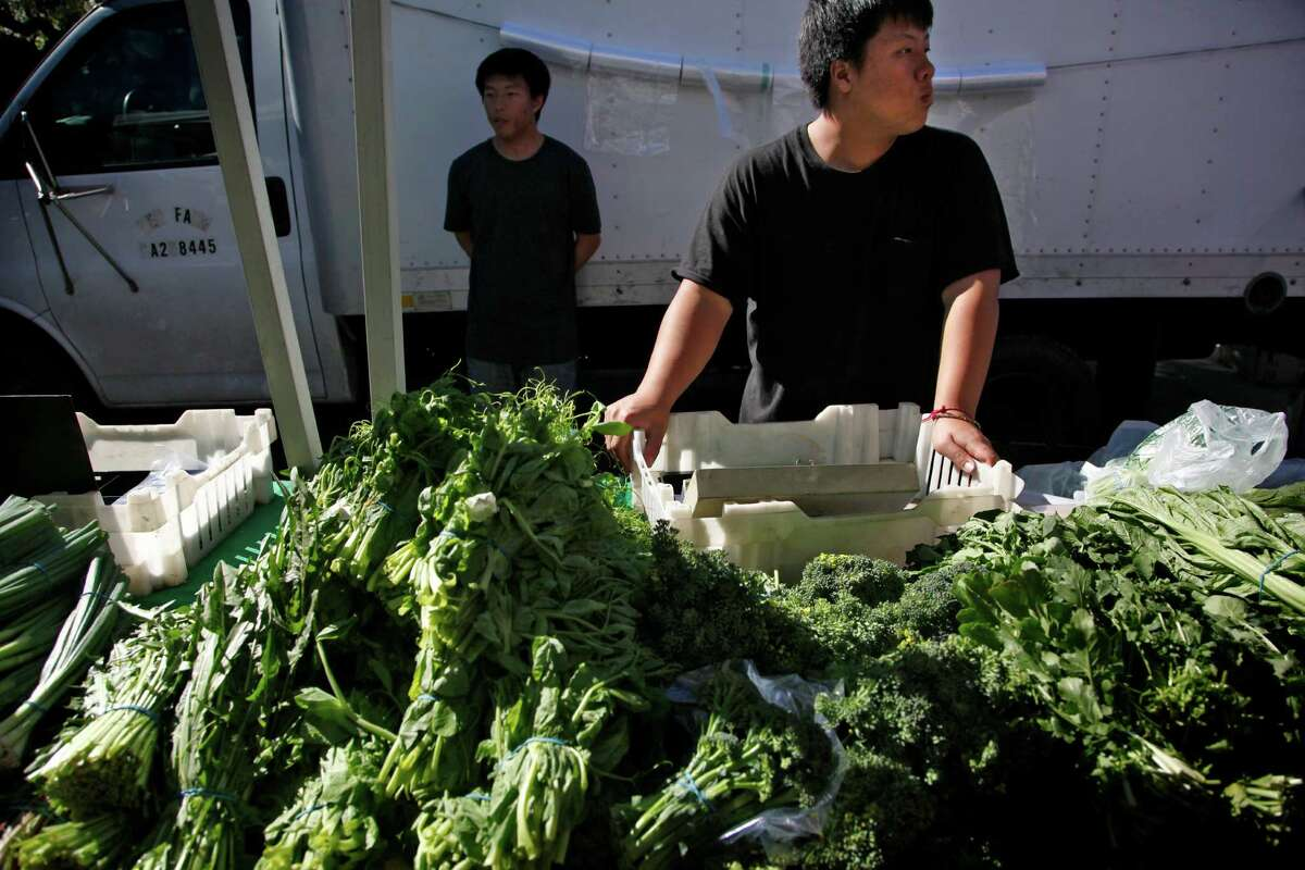 Greyshire Her (foreground) sells produce at the stall of Hmong farmer Chaving Her, who owns Her Farms in Fresno.