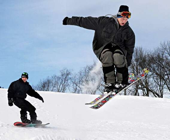 Snow boarder Mike Zampella, left, and skier Ryan Capron, both of Burnt Hills, practice a little urban free-styling on the hills behind the Glendale Home on Hetcheltown Road Tuesday Feb. 24, 2015, in Glenville, NY.  (John Carl D'Annibale / Times Union) Photo: John Carl D'Annibale
