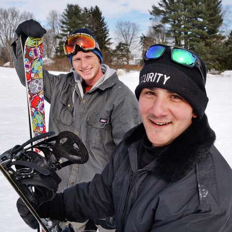 Skier Ryan Capron, left, and snow boarder Mike Zampella, both of Burnt Hills, on their way to  a little urban free-styling on the hills behind the Glendale Home on Hetcheltown Road Tuesday Feb. 24, 2015, in Glenville, NY.  (John Carl D'Annibale / Times Union) Photo: John Carl D'Annibale