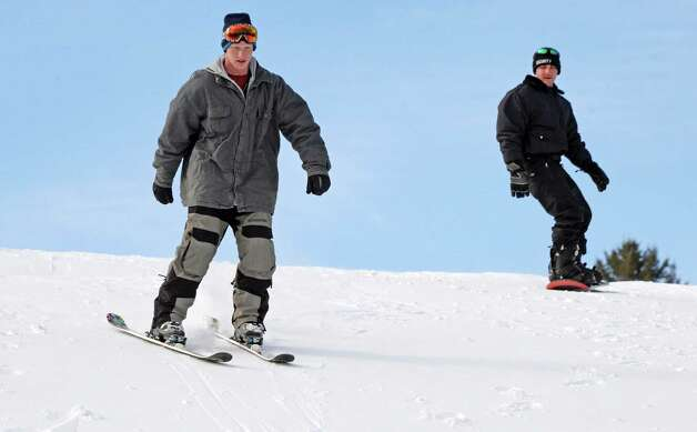 Skier Ryan Capron, left, and snow boarder Mike Zampella, both of Burnt Hills, practice a little urban free-styling on the hills behind the Glendale Home on Hetcheltown Road Tuesday Feb. 24, 2015, in Glenville, NY.  (John Carl D'Annibale / Times Union) Photo: John Carl D'Annibale
