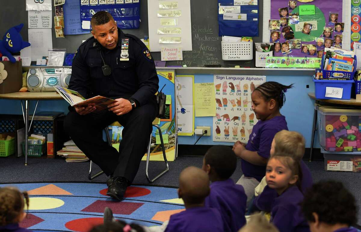 Troy Police officer Chris Johnson reads a poem by poet laureate Maya Angelou to students in Mrs. Ann Miller's kindergarten class during a Black History Month program event Tuesday morning, Feb. 24, 2015, at Public School 2 in Troy, N.Y. (Skip Dickstein/Times Union)
