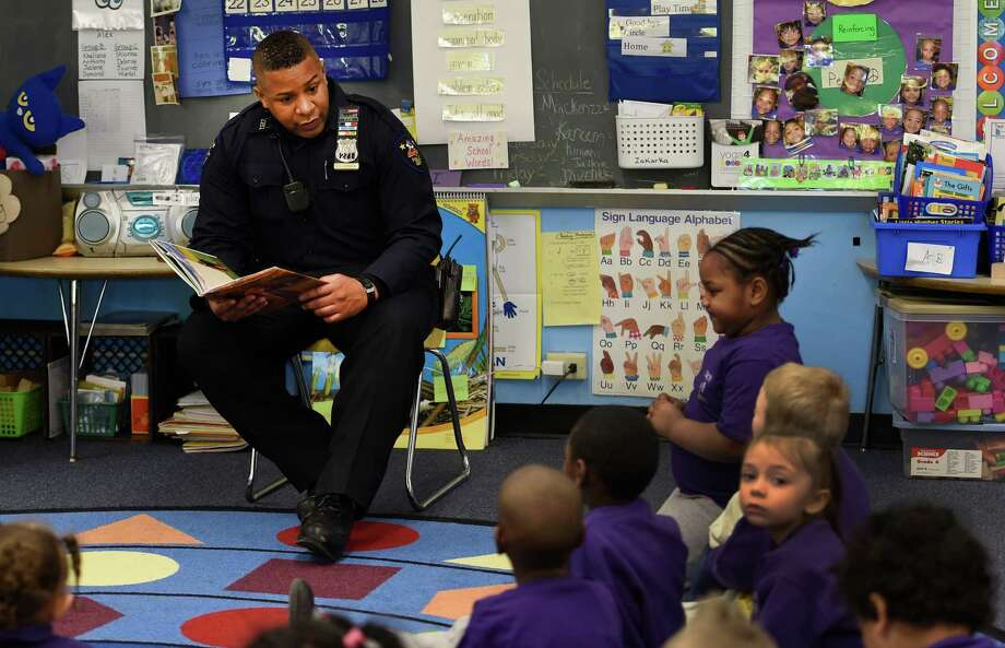 Troy Police officer Chris Johnson reads a poem by poet laureate Maya Angelou to students in Mrs. Ann Miller's kindergarten class during a Black History Month program event Tuesday morning, Feb. 24, 2015, at Public School 2 in Troy, N.Y. (Skip Dickstein/Times Union) Photo: SKIP DICKSTEIN / 00030738A