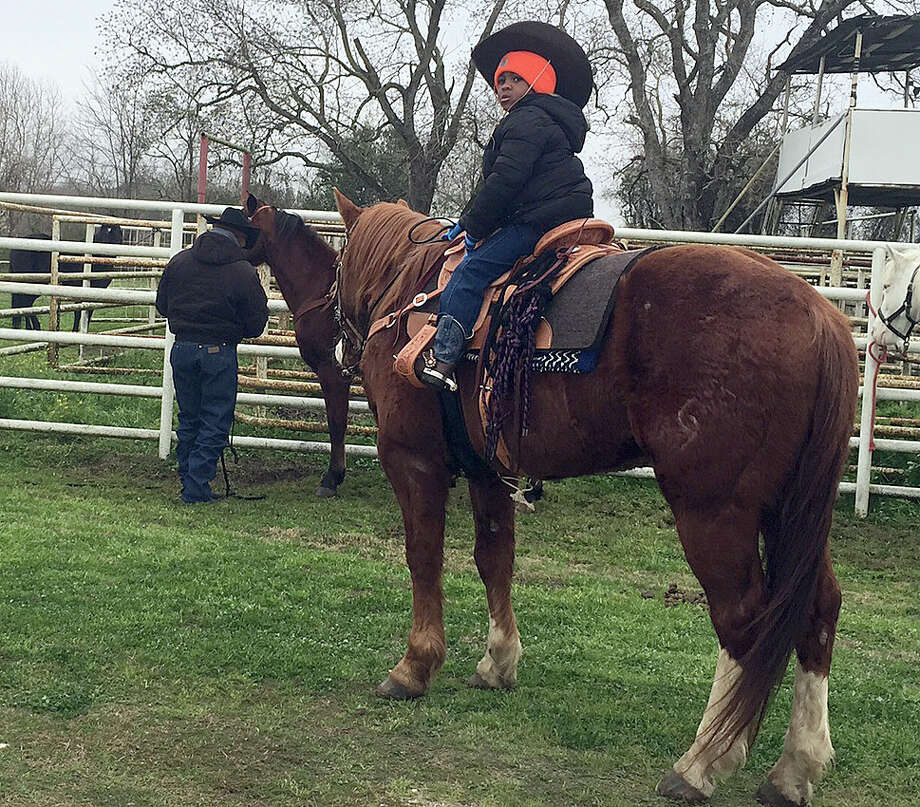 Jerry Henry Jr. warms up his horse with his dad, Jerry Henry Sr., Behind him. Photo: Leah Binkovitz / Houston Chronicle