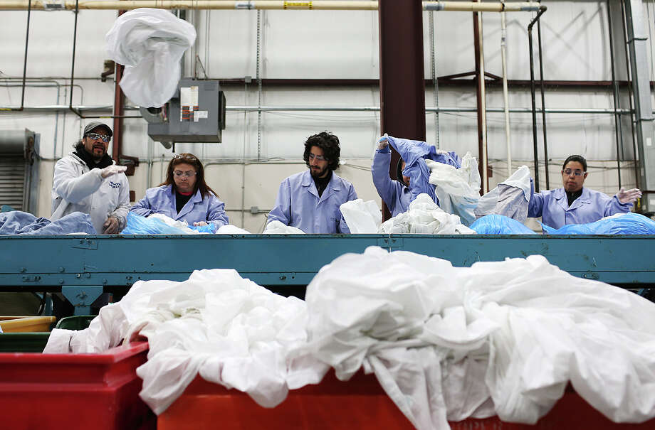 Workers divide medical facility linen Tuesday at Division Laundry & Cleaners at 6649 W. U.S. 90. Peter Garcia started the business in 1939 inside Fort Sam Houston. He would wash the soldiers' uniforms. Besides servicing area hospitals, the company also now works with hotels. Photo: Jerry Lara /San Antonio Express-News / © 2015 San Antonio Express-News