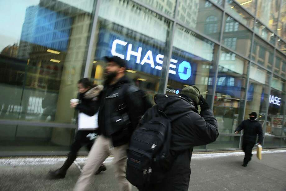 Pedestrians pass a Chase bank in Manhattan. JPMorgan Chase announced Tuesday that is cutting branches as customers continue to move online. Photo: Spencer Platt, Staff / 2015 Getty Images