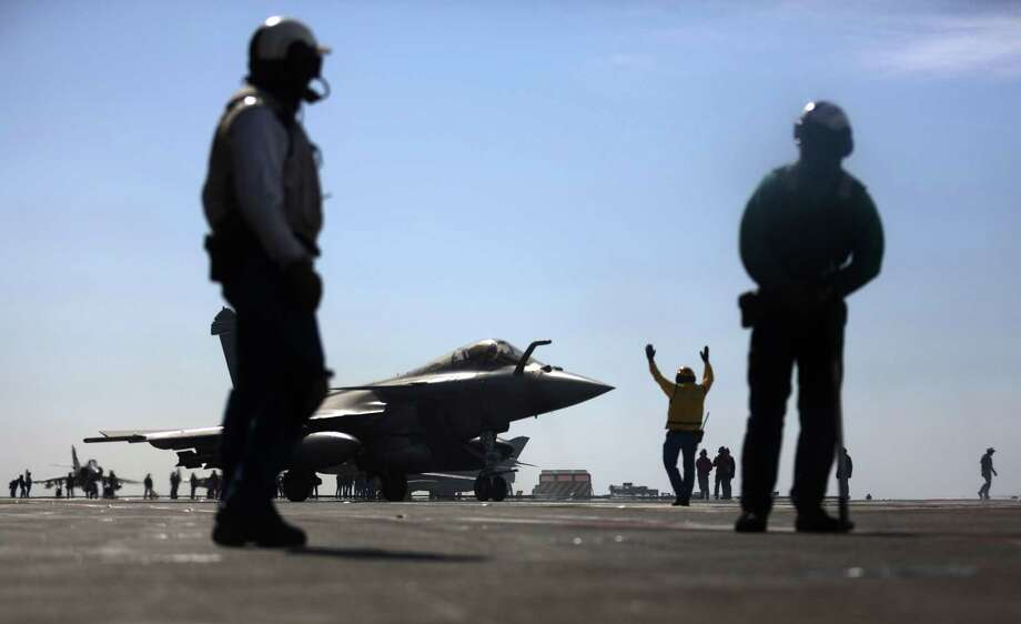 A French Navy Rafale fighter jet prepares to take off from the aircraft carrier Charles de Gaulle operating in the Persian Gulf. The carrier, with 12 Rafale and nine Super Etendard fighters, is part of the strike team hitting the Islamic State. Photo: PATRICK BAZ, Staff / AFP