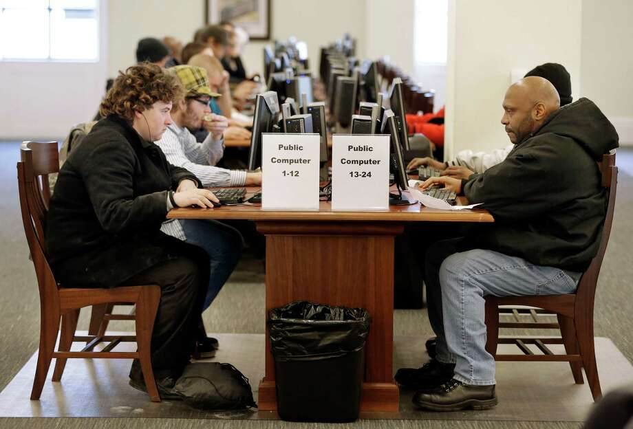 Nashville Public Library in Tennessee recently cleared books from the third floor to install 68 computers and tables with ethernet connections and power outlets, which homeless patrons like Larry Lawrence, left, utilize to stay connected. Photo: Mark Humphrey, STF / AP