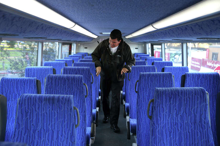 Orlando Perez of AC Transit looks for any items left behind in the upper deck after a commuter run to Stanford. Photo: Paul Chinn / The Chronicle / ONLINE_YES