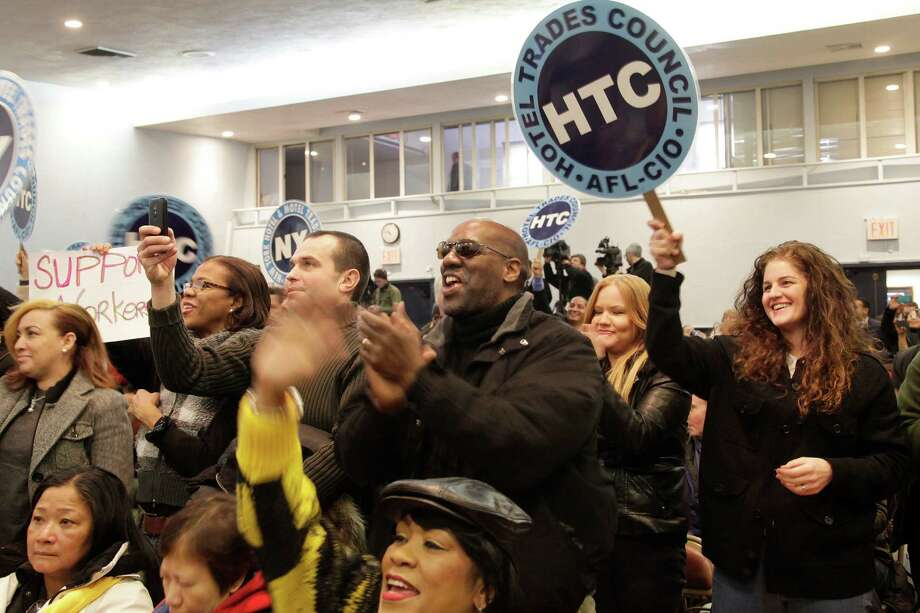 Union members of the Hotel and Motel Trades Council cheer a speech by New York Governor Andrew Cuomo, Tuesday, Feb. 24, 2015 in New York.  The Cuomo administration announced Tuesday that restaurant servers, hotel housekeepers and other tipped workers in New York will soon make $7.50 an hour before tips, a change that will translate into a big raise for thousands of workers throughout the state. (AP Photo/Mark Lennihan) ORG XMIT: NYML202 Photo: Mark Lennihan / AP