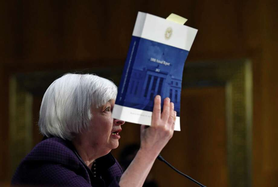 Federal Reserve Board Chair Janet Yellen holds up a copy of the 100th Annual Report from the Federal Reserve as she testifies on Capitol Hill in Washington, Tuesday, Feb. 24, 2015, before the Senate Banking Committee. Yellen said Tuesday that the U.S. economy is making steady progress, but the Fed remains patient in raising interest rates because too many Americans are still unemployed, wage growth remains sluggish and inflation is too low.  (AP Photo/Susan Walsh) Photo: Susan Walsh, STF / AP