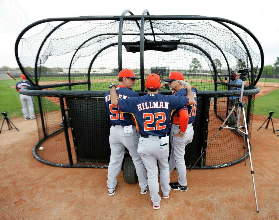 Astros bench coach Trey Hillman (22) conducts a meeting of the minds with hitting coach Dave Hudgens, left, and roving hitting instructor Ralph Dickenson on Tuesday.  See more Astros photos from Kissimmee at Chron.com/2015springtraining. Photo: Karen Warren, Staff / © 2015 Houston Chronicle