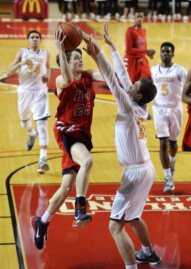 Hardin-Jefferson's Michael Saladin, No. 25, takes it up to the basket against Liberty's H. Standish, No. 20, on Tuesday. The Hardin-Jefferson Hawks played against the Liberty Panthers at the Montagne Center on Tuesday night. The final score was Hardin-Jefferson 75, Liberty 57.  Photo taken Tuesday 2/24/15  Jake Daniels/The Enterprise Photo: Jake Daniels / ©2014 The Beaumont Enterprise/Jake Daniels