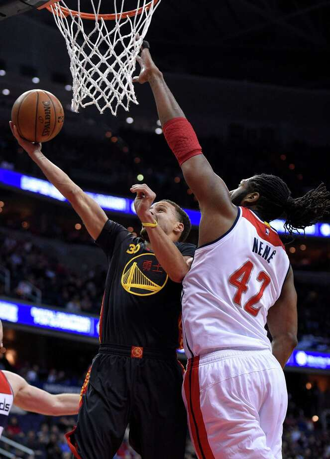 Golden State Warriors guard Stephen Curry (30) goes to the basket against Washington Wizards forward Nene (42), of Brazil, during the first half of an NBA basketball game, Tuesday, Feb. 24, 2015, in Washington. (AP Photo/Nick Wass) ORG XMIT: VZN103 Photo: Nick Wass / FR67404 AP