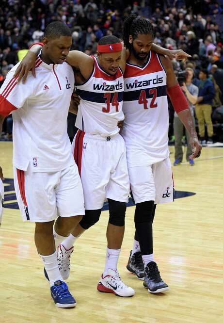 Washington Wizards forward Paul Pierce (34) is helped off the court by Kevin Seraphin, left, and Nene (42), of Brazil, after an NBA basketball game against the Golden State Warriors, Tuesday, Feb. 24, 2015, in Washington. The Warriors won 114-107. (AP Photo/Nick Wass) Photo: Nick Wass, FRE / FR67404 AP