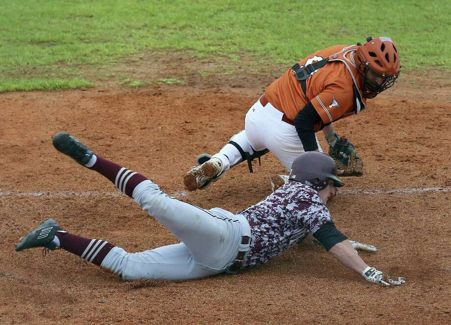 Pearland's Macord Foran, bottom, slides home ahead of the tag by Dobie catcher Adrian Rivera to score in the second inning Tuesday. Photo: Thomas B. Shea, Freelance / © 2014 Thomas B. Shea