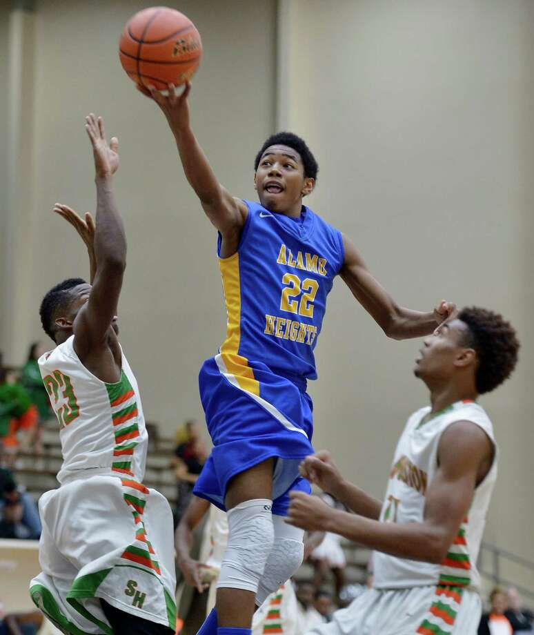 Alamo Heights' Jhonathan Dunn shoots against Sam Houston's Darrel Bledsoe (left) and Jawon Anderson on Feb. 24, 2015, at Alamo Convocation Center in San Antonio. Photo: Darren Abate /For The Express-News / Express-News