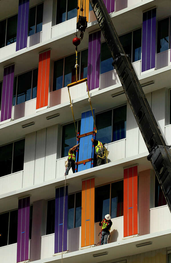 Workers place a colored panel on a ledge at Children's Hospital of San Antonio earlier this month. On Wednesday, the hospital will announce a $5 million donation from H-E-B to be used for its new emergency department. It also will announce the opening of the first phase of the emergency department, along with its outpatient pediatric service center. Photo: John Davenport /San Antonio Express-News / ©San Antonio Express-News/John Davenport