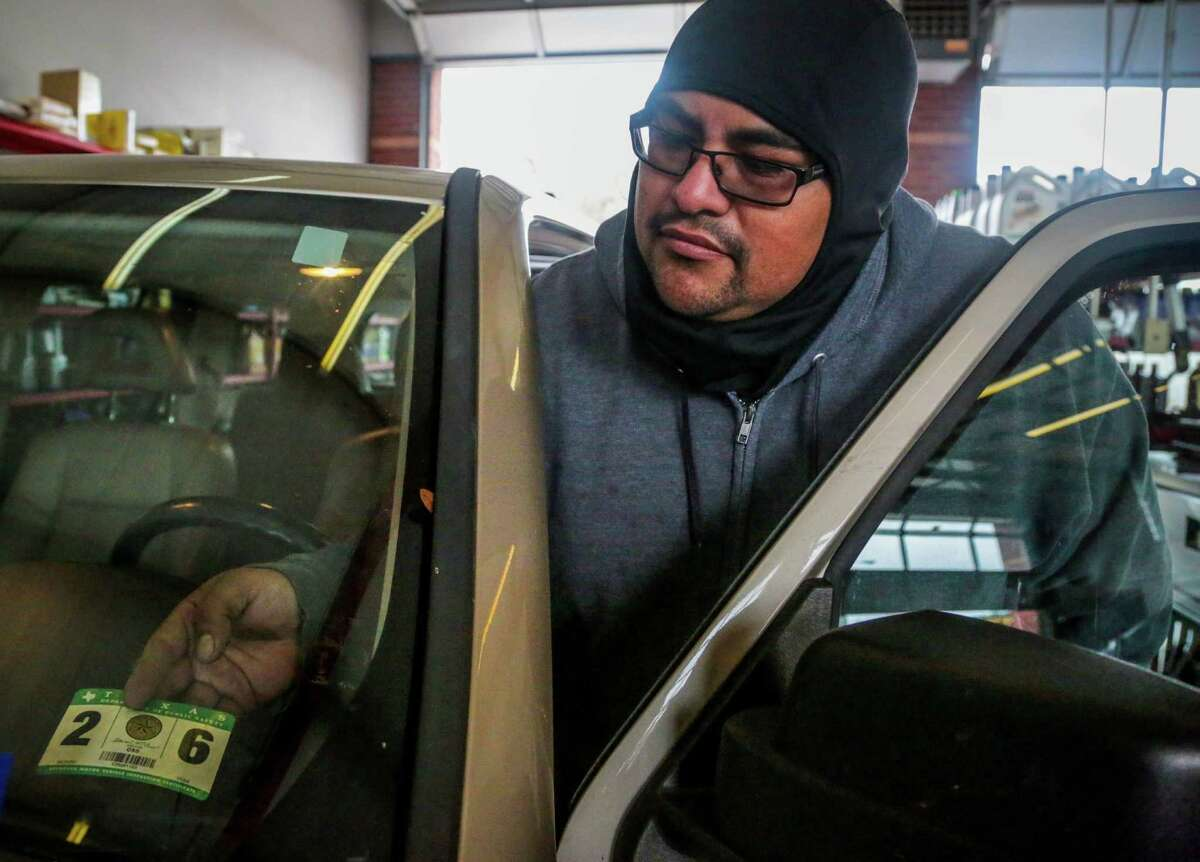 Johnny Pudildo of Kwik Kar Lube and Tune applies an inspection sticker to a customer's car Tuesday.
