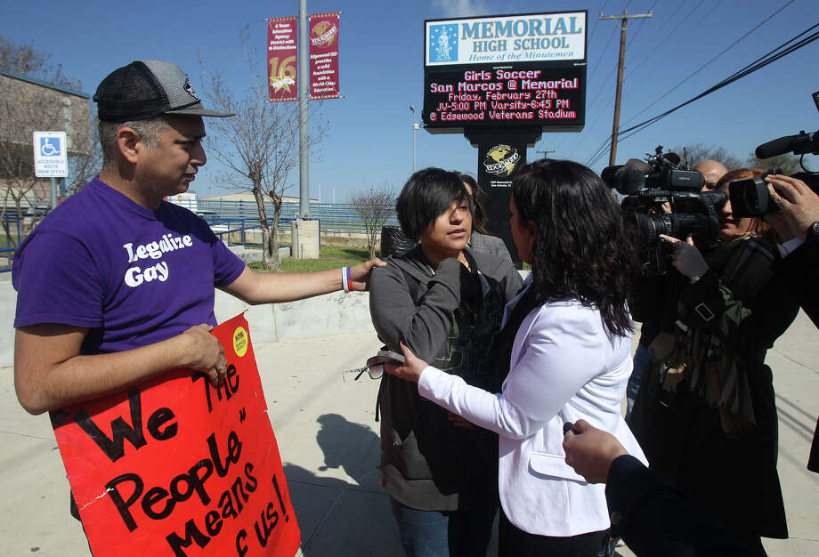 Memorial High School student Jayden Blake Castillo,18, (center) speaks with transgender activist Nikki Araguz Loyd in front of Memorial High School Wednesday February 25, 2015. Castillo, a transgender male, was protesting his treatment at the school regarding school district policy. On the left holding the sign is Carlos Soto. Photo: John Davenport, San Antonio Express-News / ©San Antonio Express-News/John Davenport