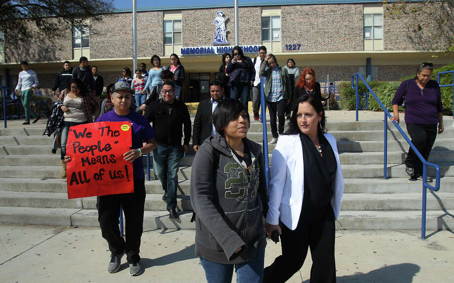 Memorial High School student Jayden Blake Castillo,18, (center) walks with transgender activist Nikki Araguz Loyd in front of Memorial High School Wednesday February 25, 2015. Castillo, a transgender male, was protesting his treatment at the school regarding school district policy. On the left holding the sign is Carlos Soto. Photo: John Davenport, San Antonio Express-News / ©San Antonio Express-News/John Davenport