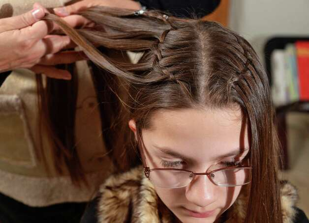 Eleven-year-old Veronica Ray has her hair braided by her mother Monica at their home Saturday Feb. 21, 2015 in Castleton-on-Hudson, NY.  (John Carl D'Annibale / Times Union) Photo: John Carl D'Annibale / 00030714A