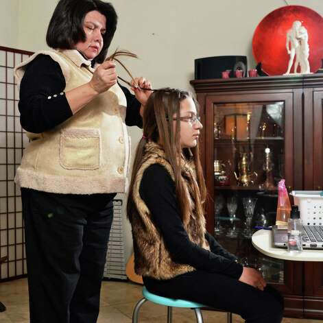 Monica Ray, left, braids her 11-year-old daughter Veronica's hair at their home Saturday Feb. 21, 2015 in Castleton-on-Hudson, NY.  (John Carl D'Annibale / Times Union) Photo: John Carl D'Annibale / 00030714A