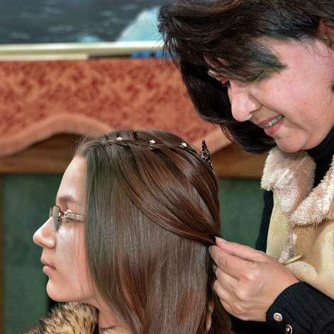 Monica Ray, right, braids her 11-year-old daughter Veronica's hair at their home Saturday Feb. 21, 2015 in Castleton-on-Hudson, NY.  (John Carl D'Annibale / Times Union) Photo: John Carl D'Annibale / 00030714A