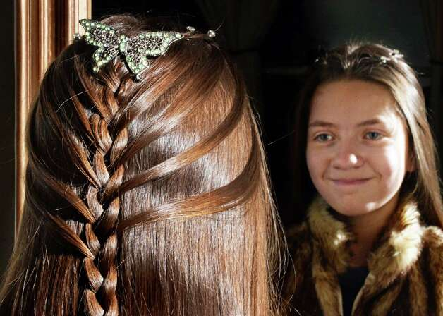 Eleven-year-old Veronica Ray looks in a mirror after having her hair braided by her mother Monica at their home Saturday Feb. 21, 2015 in Castleton-on-Hudson, NY.  (John Carl D'Annibale / Times Union) Photo: John Carl D'Annibale / 00030714A