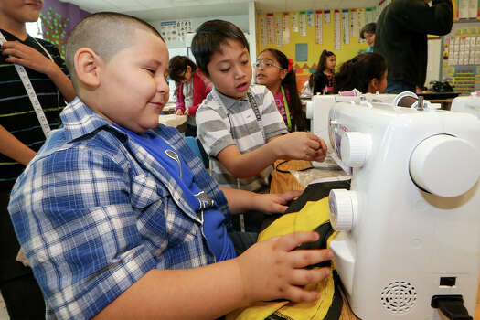 Juan Davila (left) and Jhonathan (spelling correct) Sanchez, both 7, work together on a sewing machine as they and other students in Lydia Devia's second grade class at Margil Elementary, 1000 Perez St., put weeks of learning to practice on Friday, Feb. 13, 2015, by using sewing machines to create heart-adorned pillows for Valentines Day.  MARVIN PFEIFFER/ mpfeiffer@express-news.net Photo: Marvin Pfeiffer, Staff / San Antonio Express-News / Express-News 2015