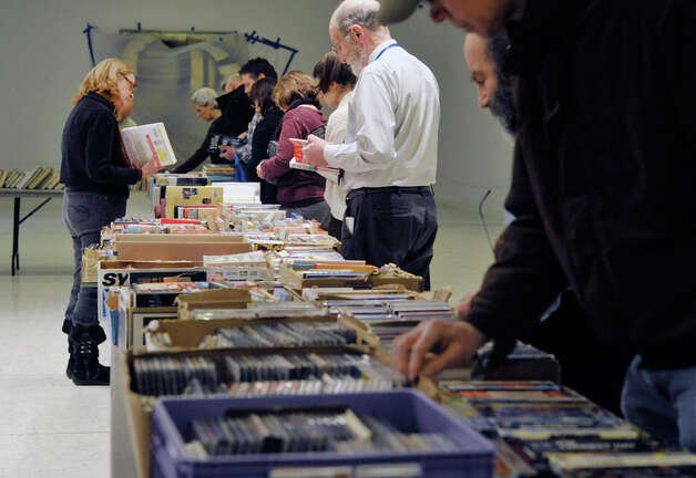 Shoppers look over the books for sale at the Help Fight Aids Through Books and Music sale on the concourse of the Empire State Plaza on Tuesday, Feb. 24, 2015, in Albany, N.Y.  Steve Kozlowski started the fund raising event in 1993 as he was looking for a way to help people dealing with aids.  The sale which is held three to four times a year at the plaza and two times a year outside The Book House in Albany, is run with donations of books and volunteers.  Kozlowski said that to date the sales have raised about $750,000, which is given to the Alliance for Positive Health.  The sale at the plaza runs through Friday.  The next sale at the concourse starts on April 28th.      (Paul Buckowski / Times Union) Photo: PAUL BUCKOWSKI, Albany Times Union / 00030679A