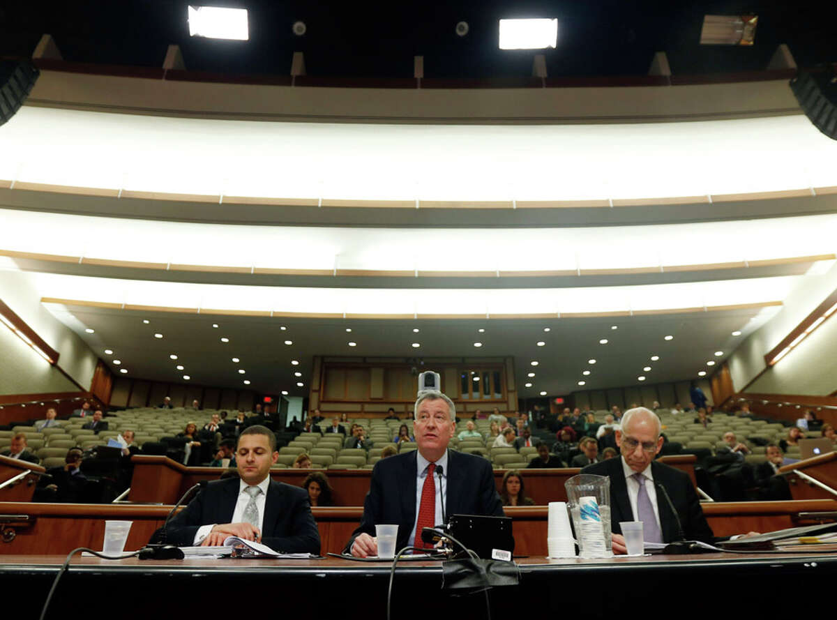New York City Mayor Bill de Blasio, center, speaks during a joint legislative budget hearing on local government on Wednesday, Feb. 25, 2015, in Albany, N.Y. Legislative affairs director Sherif Soliman, left, and the city's budget director Dean Fuleihan, listen. (AP Photo/Mike Groll) ORG XMIT: NYMG102
