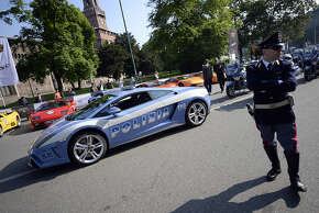 An Italian police officer walks in front of one of the two Lamborghini cars owned by the Italian Police, on May 8, 2013 in Milan. Two hundred and fifty vintage and modern Lamborghini cars will parade through Italian cities, starting from downtown Milan, to celebrate the 50th anniversary of the brand. AFP PHOTO / OLIVIER MORIN
