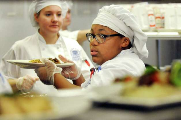 Culinary student Tia Carter, center, finishes a plate in the kitchen at the Casola Dining Room on Wednesday, Feb. 18, 2015, at Schenectady County Community College in Schenectady, N.Y. (Cindy Schultz / Times Union) Photo: Cindy Schultz / 00030647A