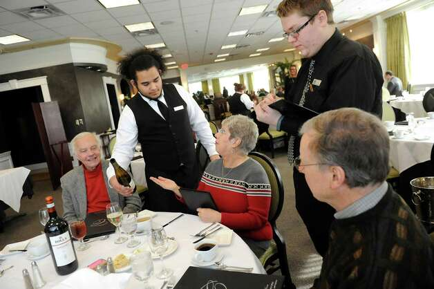 Culinary students Joseph Smith, center, and Alex Ognan, right, wait on guests at the Casola Dining Room on Wednesday, Feb. 18, 2015, at Schenectady County Community College in Schenectady, N.Y. The guests, who are regulars, from left are Bruce Dieffenbach, Mary Ann Marshall and her husband Alan Marshall. (Cindy Schultz / Times Union) Photo: Cindy Schultz / 00030647A
