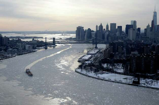 A boat makes its way through ice on the East River in New York, Tuesday, Feb. 24, 2015. The Weather Service said temperatures would be 15 to 25 degrees below average for most of the East Coast west to the Great Lakes and lower Mississippi River Valley. (AP Photo/Seth Wenig) ORG XMIT: NYSW103 Photo: Seth Wenig, AP / AP
