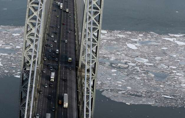 Ice floats under the George Washington Bridge on the Hudson River in New York, Tuesday, Feb. 24, 2015. A wide swath of the country is experiencing record-breaking temperatures while other areas are expecting more winter precipitation Tuesday. (AP Photo/Seth Wenig) ORG XMIT: NYSW113 Photo: Seth Wenig, AP / AP